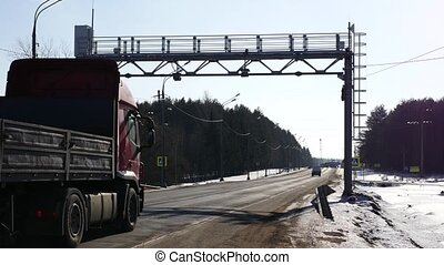 trucking on road going under Multi lane free flow traffic control frame