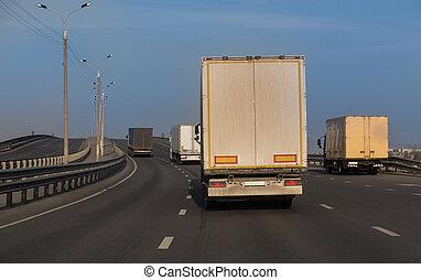 Trucks are moving across the bridge on highway