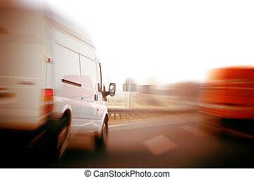 Transportation, logistics concept. Delivery vans, trucks on a freeway, speed motion blur.
