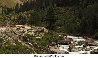 Trucks driving alongside a river with sightseers - Extreme...