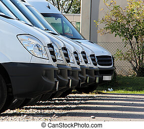 trucks in a row - white delivery cars are waiting for some...