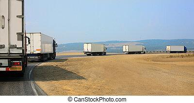 escort of trucks moves on mountain road