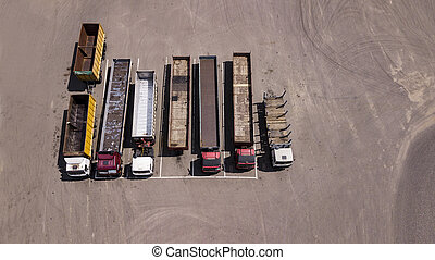 trucks stand in a row Parking lot - top view from the drone