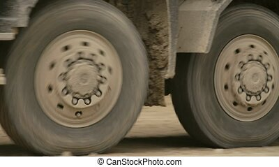 Truck's wheels driving on a dirt road