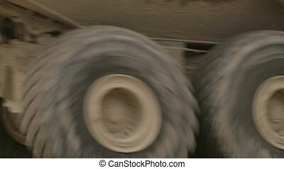 Truck's wheels on a dirt road.