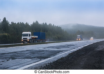 trucks with containers go in the fog along the highway