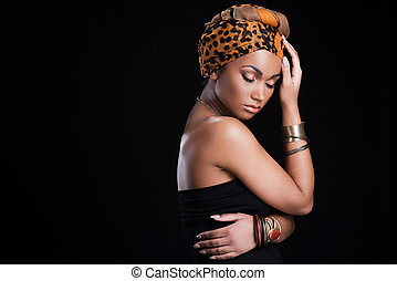 True African beauty. Beautiful African woman wearing a headscarf and posing against black background