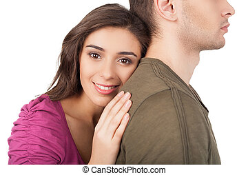 True love. Cheerful young woman hugging her boyfriend and looking at camera while standing isolated on white