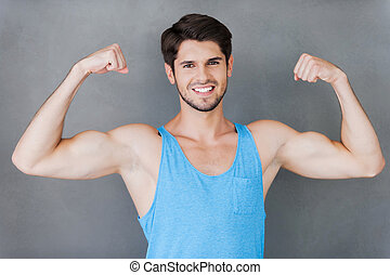 True masculinity. Handsome young muscular man showing his perfect biceps while standing against grey background