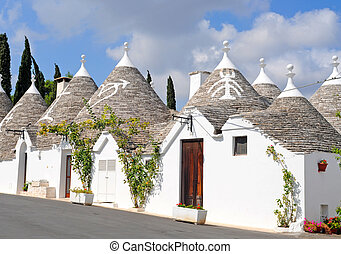 Trulli houses with painted symbols on the conical roofs in...