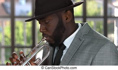 Trumpet player indoors. Musician in a hat. Beauty of jazz.