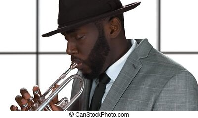Trumpet player isolated. Black musician in a hat.