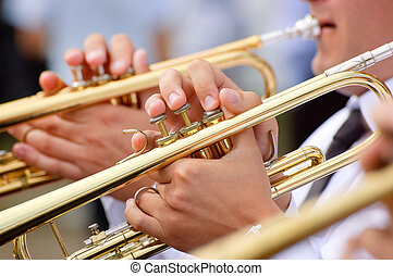 Group of young musicians playing on trumpets