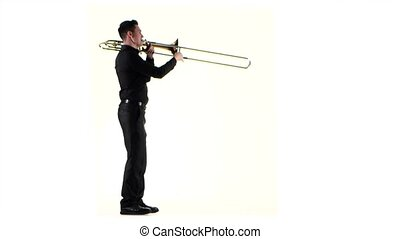 Trumpeter plays on wind instrument fast melody in white studio