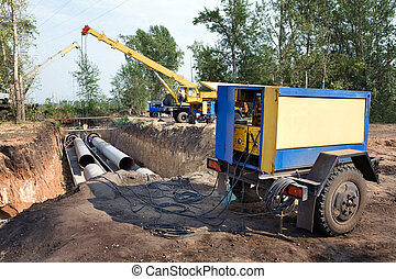 A group of workers are constructing a trunk pipeline in the ditch.