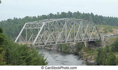 Steel Pratt truss bridge over the French River. Black pickup truck passes. HWY 69, Killarney, Ontario, Canada.
