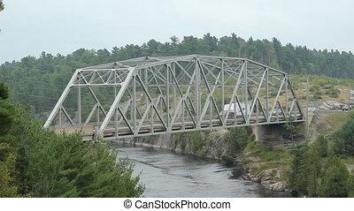 Steel Pratt truss bridge over the French River. Camper and traffic passes. HWY 69, Killarney, Ontario, Canada.