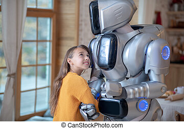 Cute girl in orange shirt feeling comfortable with her house robot