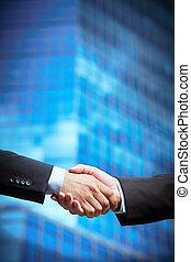 Trust - Vertical image of entrepreneurs hands concluding a...