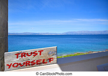 Trust yourself on old plank with blurred sea background