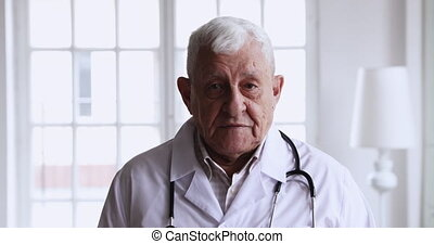 Trustful respectful old therapist giving professional consultation to patient.