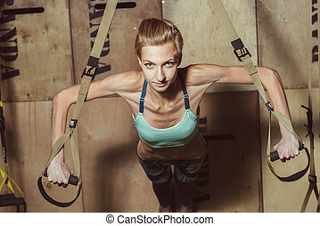 TRX. Girl doing exercises in the hall