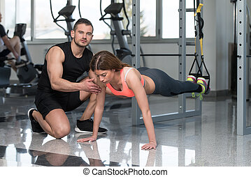 Trx Straps Training - Personal Trainer Showing Young Woman...