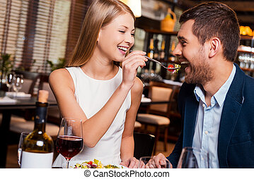 Try my meal! Beautiful young loving couple enjoying dinner...