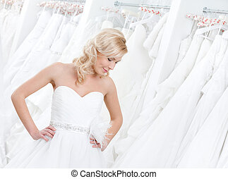 Trying on an amasing wedding gown - Youg girl is trying on...