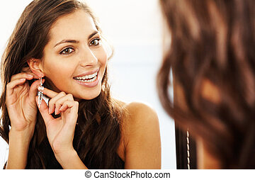 Trying on earrings - Image of pretty female looking in ...