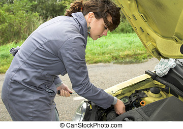 Trying to fix the car - Pretty brunette trying to fix her...