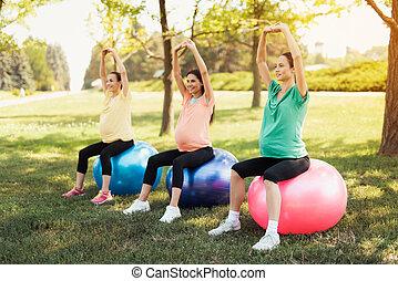 trzy, brzemienne kobiety, czas teraźniejszy czasownika be, posiedzenie, w, niejaki, park, na, yoga, piłki, z, ich, ręki do góry