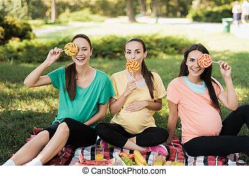 trzy, brzemienne kobiety, przedstawianie, w, niejaki, piknik, park, z, wielki, barwny, kandyz