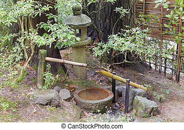 Tsukubai Water Fountain and Stone Lantern in Japanese Garden