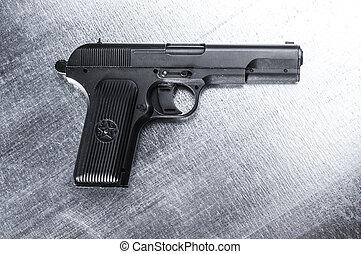 TT pistol. Soviet gun on vintage metal background.