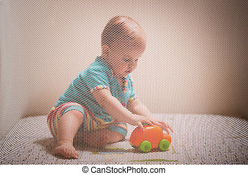 ttle kid playing with toys in a playpen