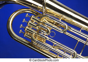 A gold brass tuba euphonium baritone horn isolated against a blue background in the horizontal format.