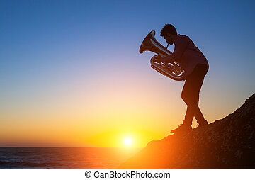 Tuba - instrument. Silhouette of a young man playing the trumpet on rocky sea coast during sunset.