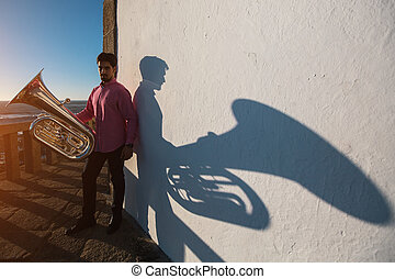 Tuba - instrument. Young man standing with trumpet in hand, a big shadow on a white wall.