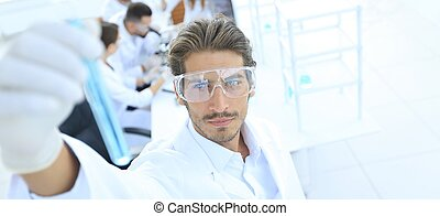 tube with reagents on blurred background laboratory.