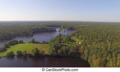 Tubes or pipes of Belarusian nuclear power plant on horizon in the distance (Astravets, Ostrowiec city). Drone aerial shot. Stracha river, beautiful european forest