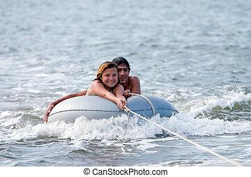 Man and girl on tube in water being towed by boat.