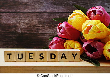 Tuesday alphabet letter and tulip flowers bouquet on wooden background