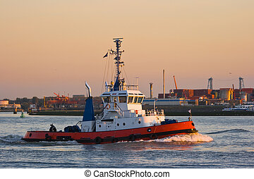 Tug passing by on the river at sunset