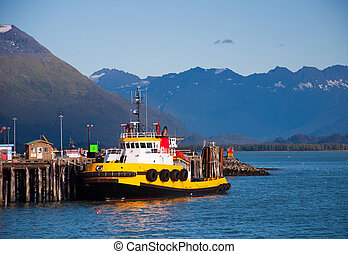 Tug Boat at Rest - View of yellow tug boat tied up at docks ...
