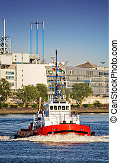 tug boat navigating a harbor river in late sun