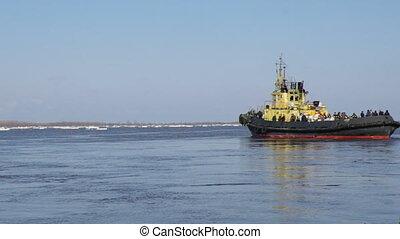 tug boat pushing through ice on a sunny springtime day