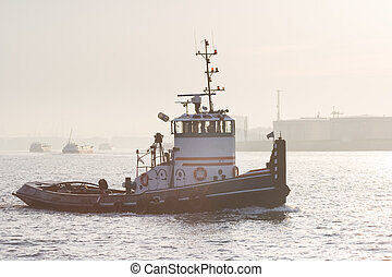 Tug sailing on the river in morning light