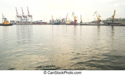 Tugboat and harbor cranes. Port at daytime. Marine industry...