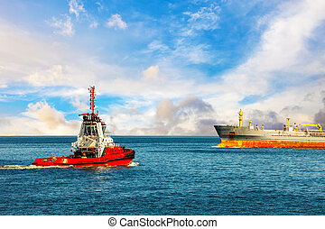 Red tug boat approaching to assist tanker.
